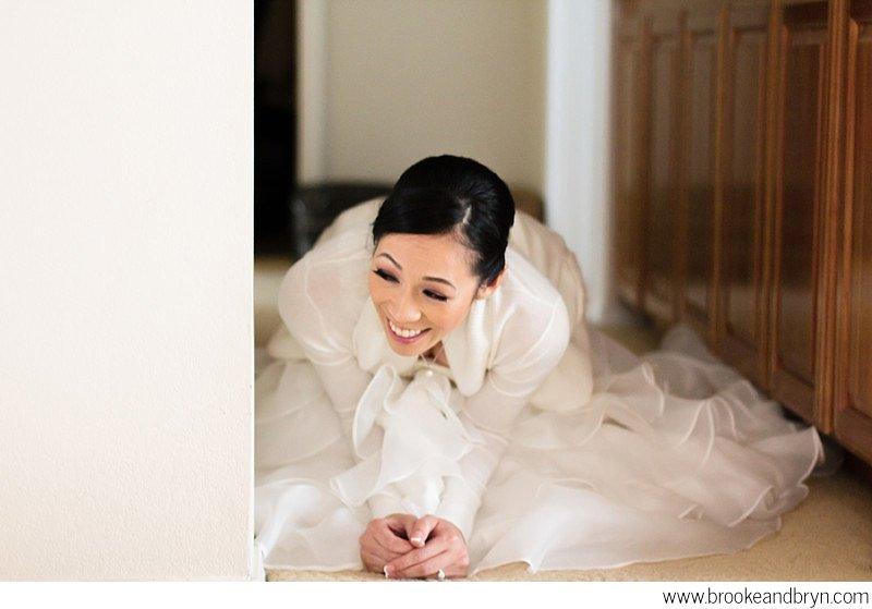 Bride sneaking a peak of her groom performing door games at a Chinese tea ceremony